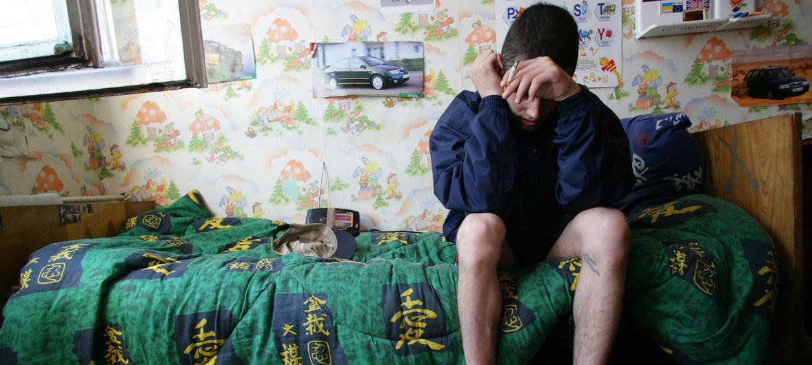Un muchacho de 19 años se sienta en su cama en un refugio para niños que viven o trabajan en las calles, en Odessa, Ucrania. El joven consume de drogas y tiene VIH, pero no tiene acceso a medicamentos antirretrovirales.