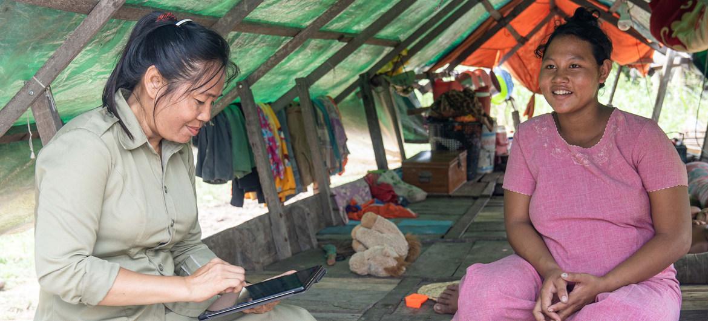 Una trabajadora registra a una mujer apta para la tarjeta de transferencias de dinero.