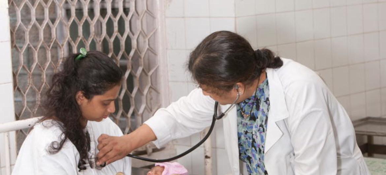 Un doctor examina a una madre con VIH y su bebé recien nacido en India.