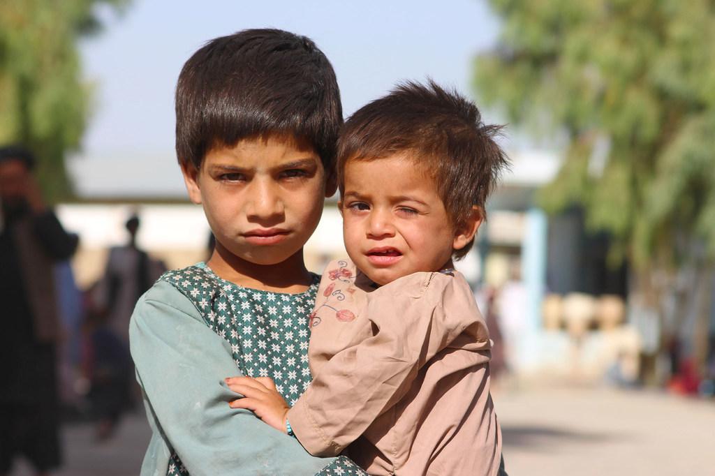 Un niño de cinco años sostiene a su hermano menor en un campo de desplazados en Kandahar, al sur de Afganistán.
