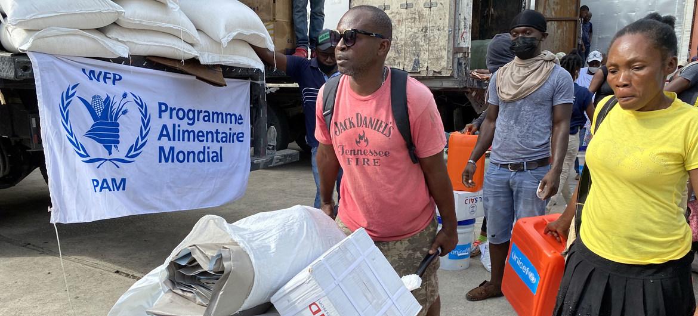 Haitianos afectados por el reciente terremoto reciben suministros de ayuda de las agencias humanitarias en la localidad de Les Cayes.