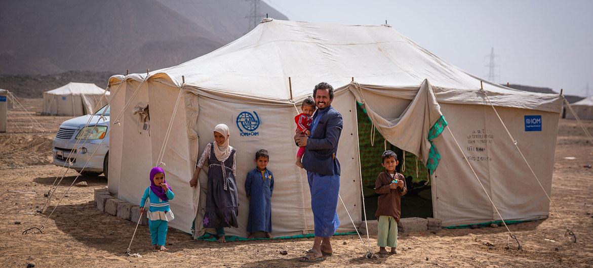 Un padre con sus hijos afuera de su tienda en un campamento de desplazados en las afueras de la ciudad de Marib, en Yemen.