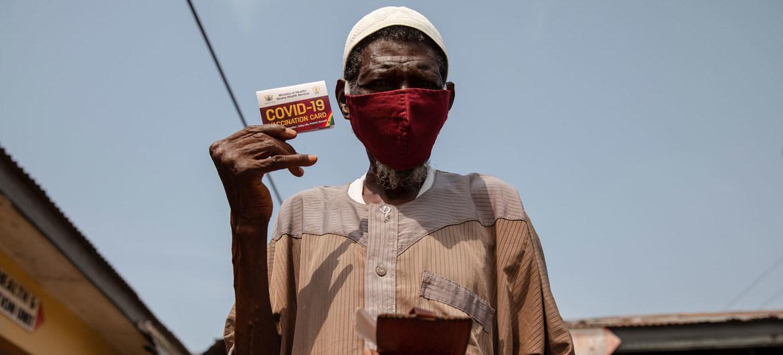 Un hombre de 76 años muestra su tarjeta de vacunación contra la COVID-19 en Kasoa, Ghana.