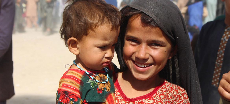 Una niña de siete años sostiene a su hermana menor en un campo de desplazados internos en Kandahar, al suroeste de Afganistán.
