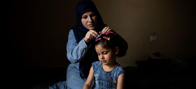 Wafaa, una refugiada siria de 32 años, sujeta el pelo de su hija Yasmine en su casa de Barja, Líbano. Las dos esperan su reasentamiento en Noruega.