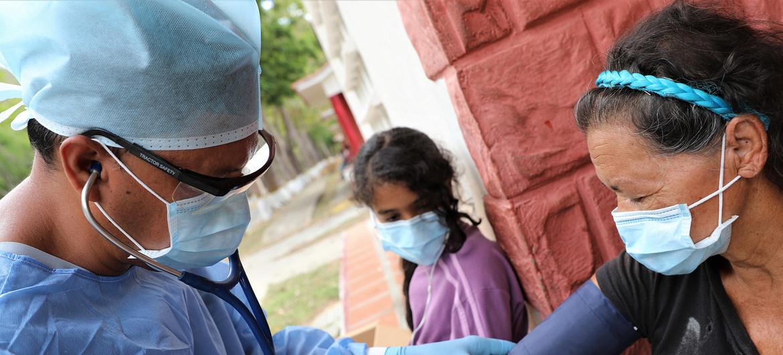 El Dr. Douglas Martínez toma la presión arterial de un migrante venezolano que regresa a la cuarentena en un refugio temporal durante Covid-19.