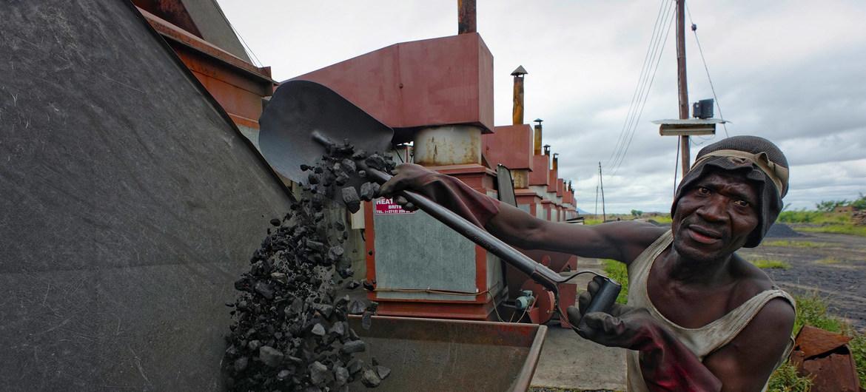Un trabajador llena de carbón una caldera en una empresa de producción de tabaco en Malawi