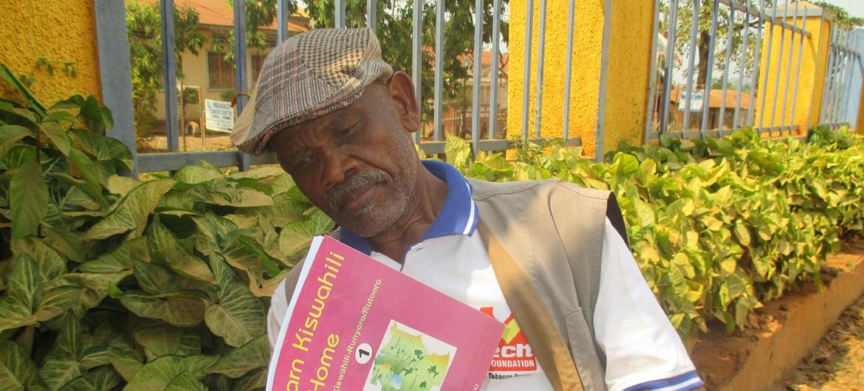 Peter Semiga, un hombre de edad de Uganda, leyendo un libro.