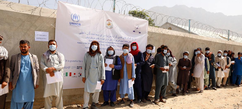 Personas desplazadas hacen cola en un centro de distribución en Afganistán.